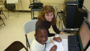 a volunteer teaching a young boy